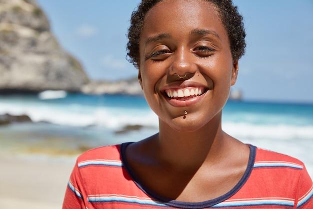Foto brilhante de uma linda garota feliz com pele morena saudável e sorriso largo