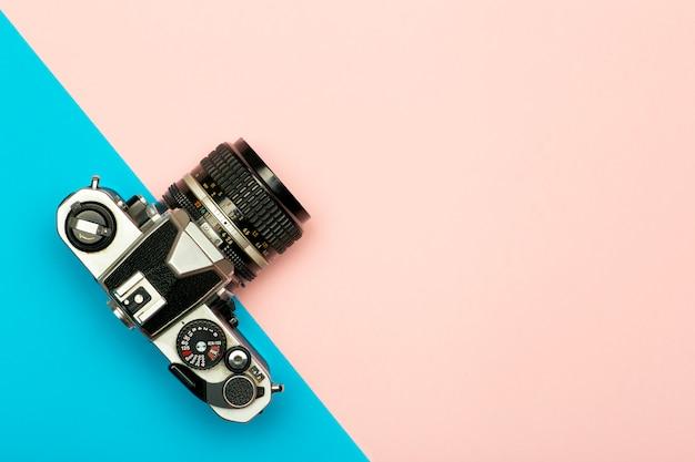 Foto câmera conceito criativo plano de fundo. câmera fotográfica retrô vintage em um fundo colorido. conceito de viagens, férias e fotografia