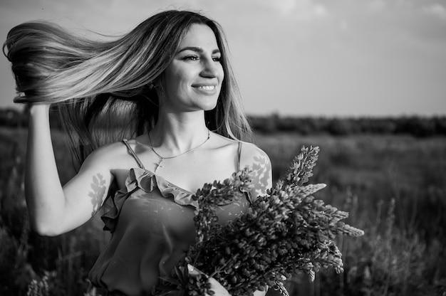 Foto cinza mulher em pé de camisa no campo com o buquê de flores