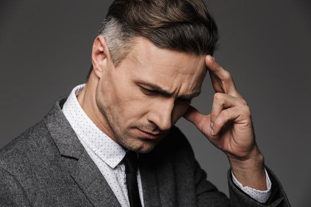 Foto closeup de homem adulto bonito 30 anos olhando para baixo e concentrando-se com o toque na testa com o dedo, isolado sobre a parede cinza