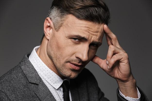 Foto closeup de homem adulto confiante 30 anos, mantendo o dedo na testa, isolado sobre a parede cinza