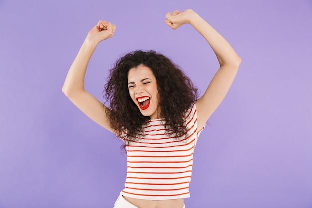 Foto closeup de mulher excitada com cabelos cacheados no desgaste do verão gritando com os braços levantados
