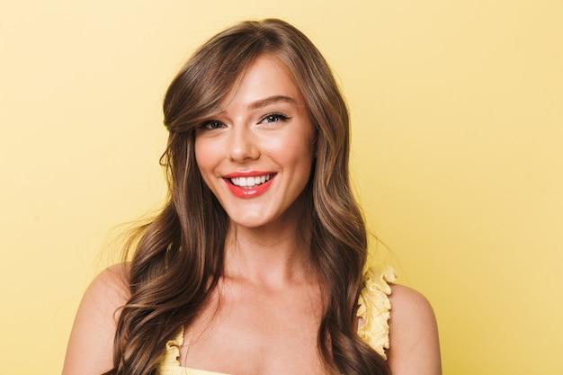 Foto closeup de uma adorável jovem de 20 anos com longos cabelos castanhos e lábios vermelhos sorrindo para você com dentes brancos perfeitos, isolados sobre um fundo amarelo