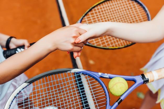Foto closeup. meninas de mãos apertando as mãos na quadra de tênis, equipe.