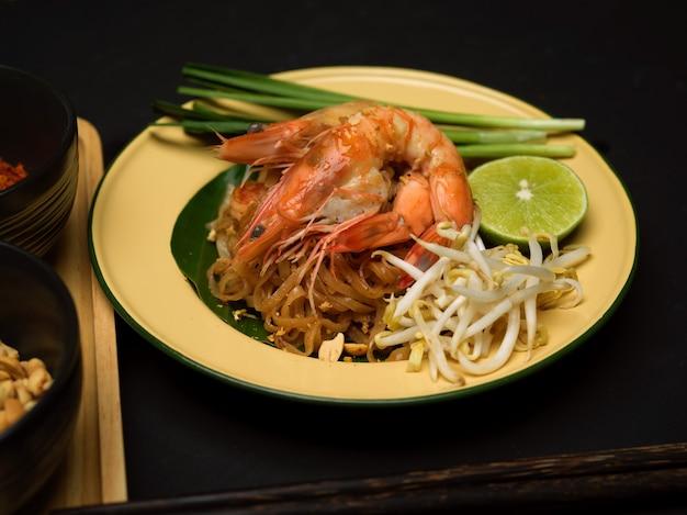 Foto colhida de macarrão tailandês refogado com camarão servindo em prato tradicional com limão, broto de feijão e cebolinha, pad thai
