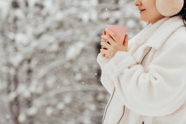 Foto colhida em close-up de uma garota bebendo chá quente ou café com árvores nevadas