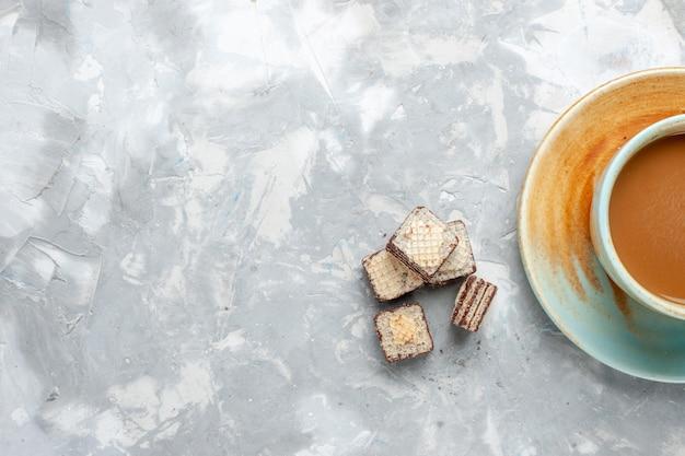 Foto colorida de bebida de leite doce com waffles e café na mesa branca
