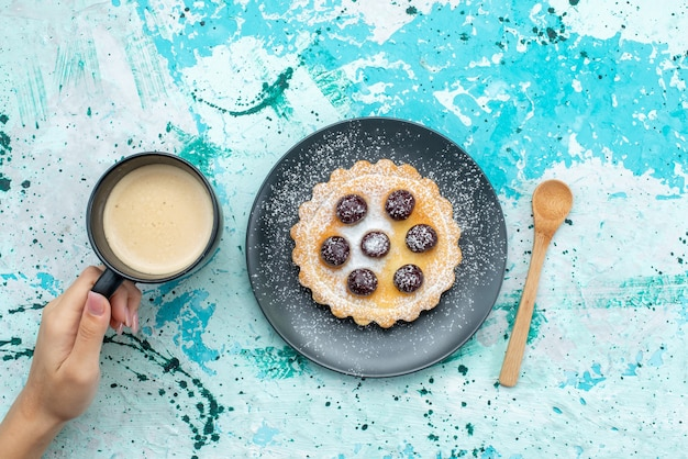 Foto colorida de bolo de açúcar em pó com frutas junto com leite na mesa azul