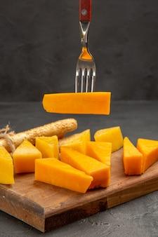 Foto colorida de café da manhã com queijo fresco fatiado com pãezinhos na refeição escura