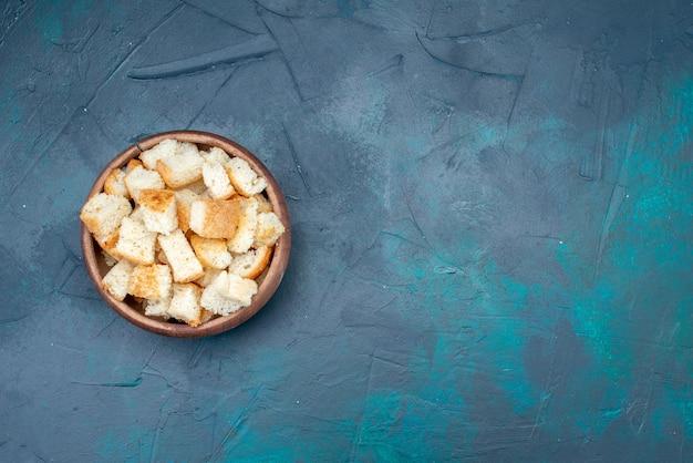 Foto colorida de lanche de bolachas em fatias de pão dentro de uma tigela marrom na mesa azul-escura