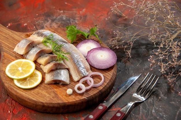 Foto colorida de peixe fresco fatiado com anéis de cebola e limão na refeição escura de carne e frutos do mar