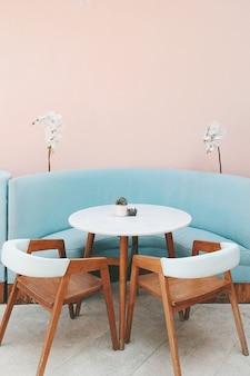 Foto colorida de sofá moderno azul claro, mesa de madeira branca
