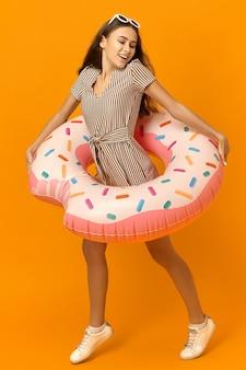 Foto colorida de uma jovem enérgica e despreocupada, vestida com roupas elegantes de verão