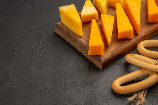 Foto colorida do café da manhã em fatias de queijo fresco com biscoitos doces em uma refeição escura