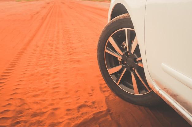 Foto com detalhe da roda de um carro de esportes branco em uma estrada de terra com fundo desfocado.