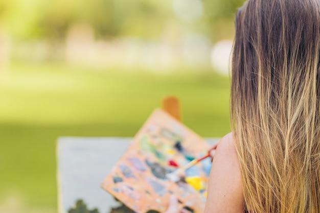 Foto com espaço de cópia e foco seletivo nas costas de uma mulher em frente a uma tela pintada em um parque