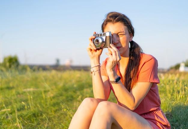 Foto com foco raso de uma jovem tirando uma foto no parque