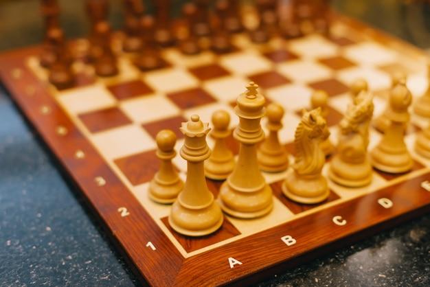 Foto com foto seletiva de um tabuleiro de xadrez de madeira.