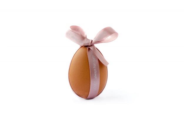 Foto com ovo da páscoa alaranjado e fita cor-de-rosa em um fundo branco.