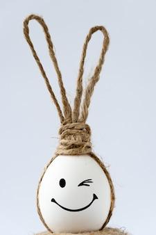 Foto com ovo de páscoa com orelhas de coelho. sorriso feliz.