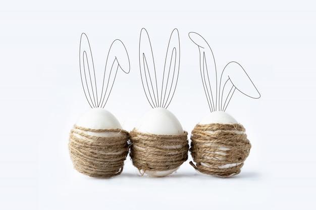 Foto com ovos da páscoa brancos com orelhas de coelho.