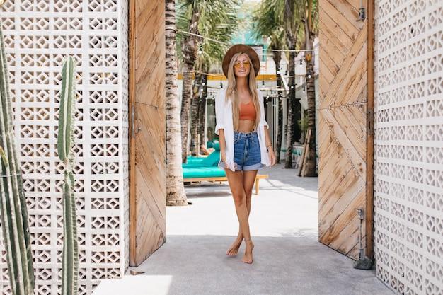 Foto completa da feliz garota magro em pé com as pernas cruzadas na manhã de verão. retrato ao ar livre da magnífica mulher loira se divertindo durante o fim de semana no resort.