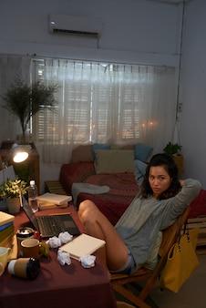 Foto completa da jovem sentada no quarto no laptop com papéis amassados