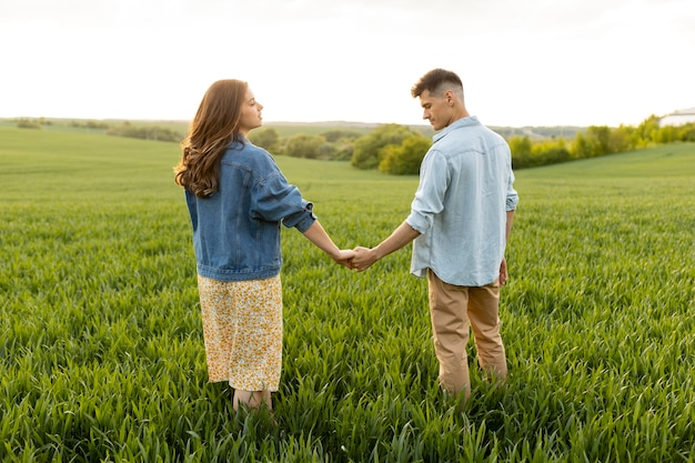 Foto completa de casal de mãos dadas ao ar livre