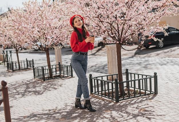 Foto completa de garota de jeans e suéter andando no jardim com um copo de café. adolescente de boina curtindo o sol e bebendo chá