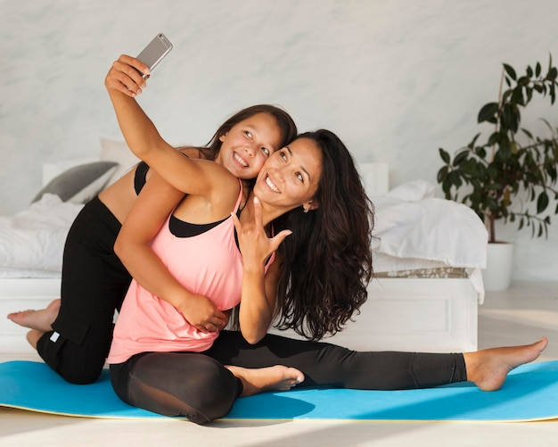 Foto completa de garota e mulher tirando uma selfie