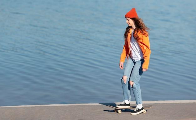Foto completa de jovem andando de skate à beira do lago