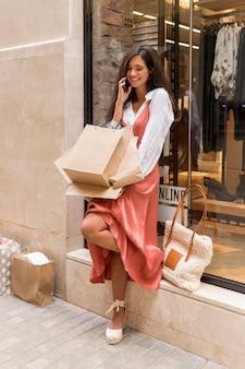 Foto completa de mulher com sacolas de compras e smartphone