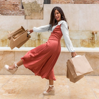 Foto completa de mulher com sacolas de compras