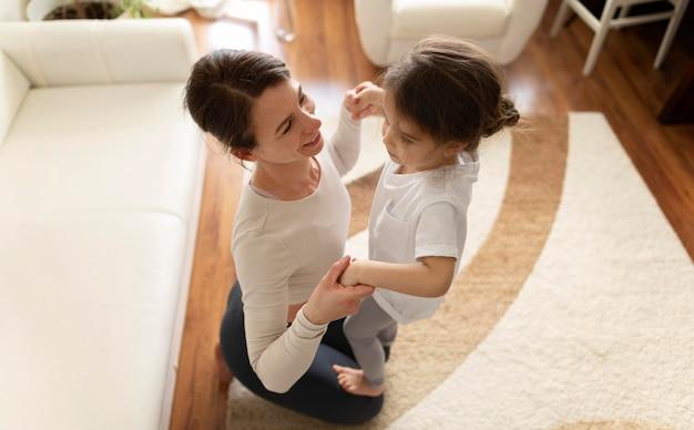 Foto completa de mulher e menina malhando no chão