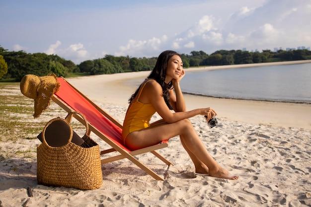 Foto completa de mulher na praia com câmera