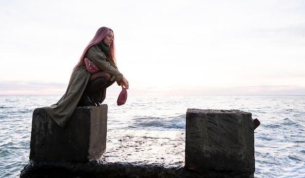 Foto completa de mulher posando à beira-mar