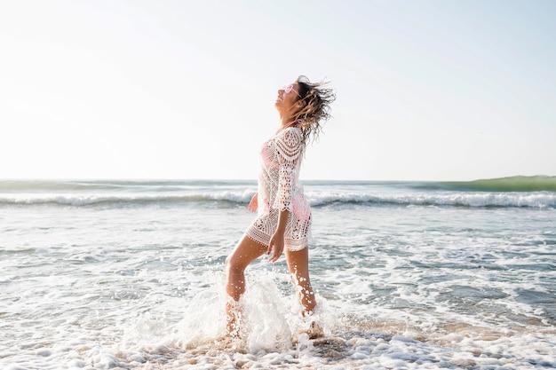 Foto completa de mulher posando na praia