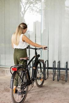 Foto completa de mulher segurando bicicleta