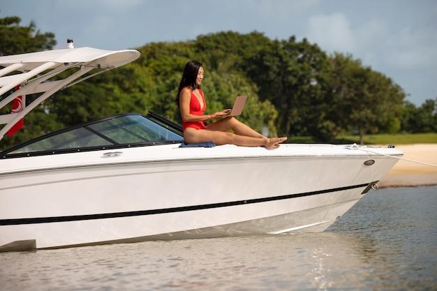 Foto completa de mulher segurando laptop no barco