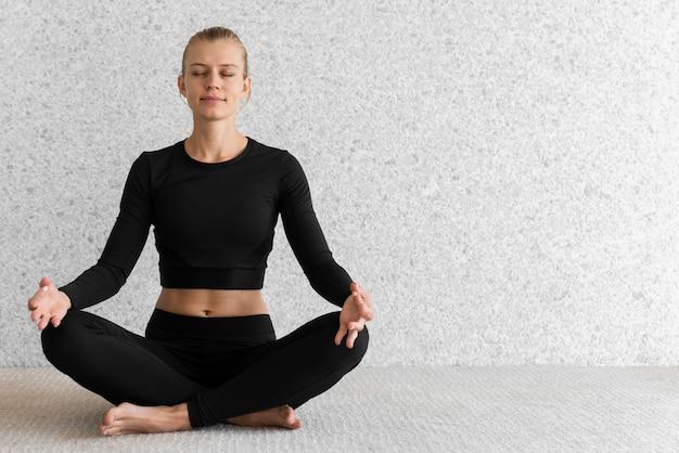 Foto completa de mulher sentada em pose de ioga