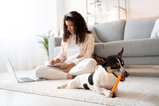 Foto completa de mulher sentada no chão com um laptop