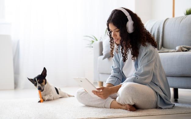 Foto completa de mulher sentada no chão com um tablet
