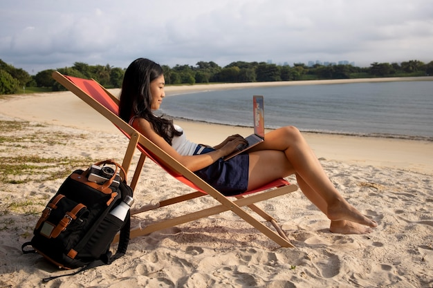 Foto completa de mulher trabalhando em um laptop ao ar livre