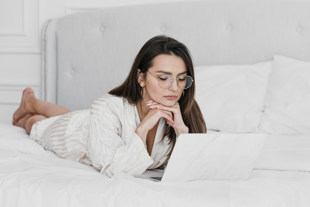 Foto completa de mulher trabalhando na cama com um laptop