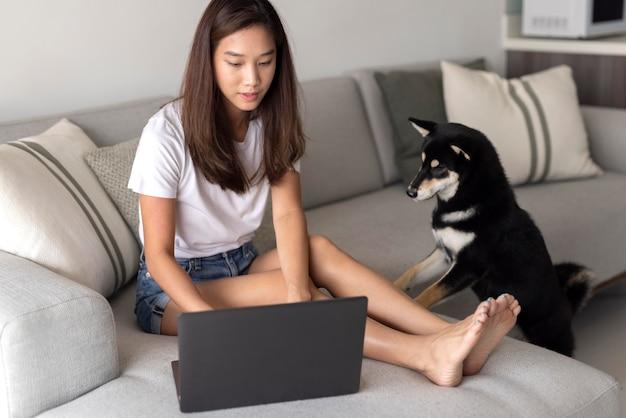Foto completa de mulher trabalhando no sofá com um cachorro fofo