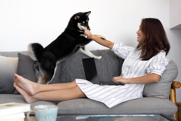 Foto completa de mulher trabalhando no sofá com um cachorro