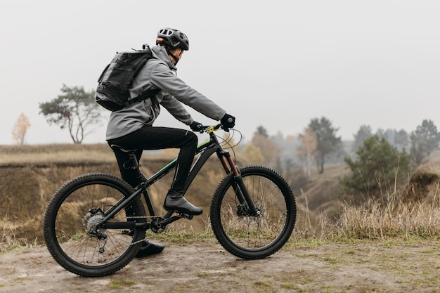 Foto completa de um homem andando de bicicleta