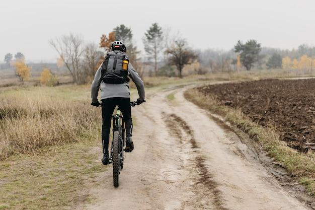 Foto completa de um homem andando de bicicleta Foto gratuita