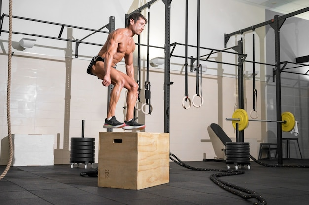 Foto completa de um jovem desportista caucasiano treinando sozinho fazendo exercícios de salto de caixa no ginásio