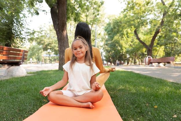 Foto completa de uma garota e uma mulher meditando no parque